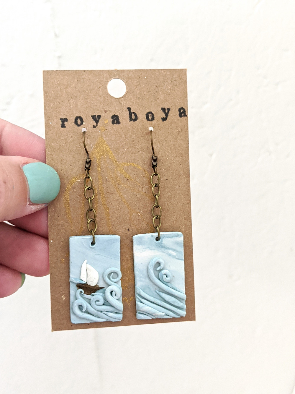 a hand holding earrings that are rectangle with an ocean and boat made out of clay