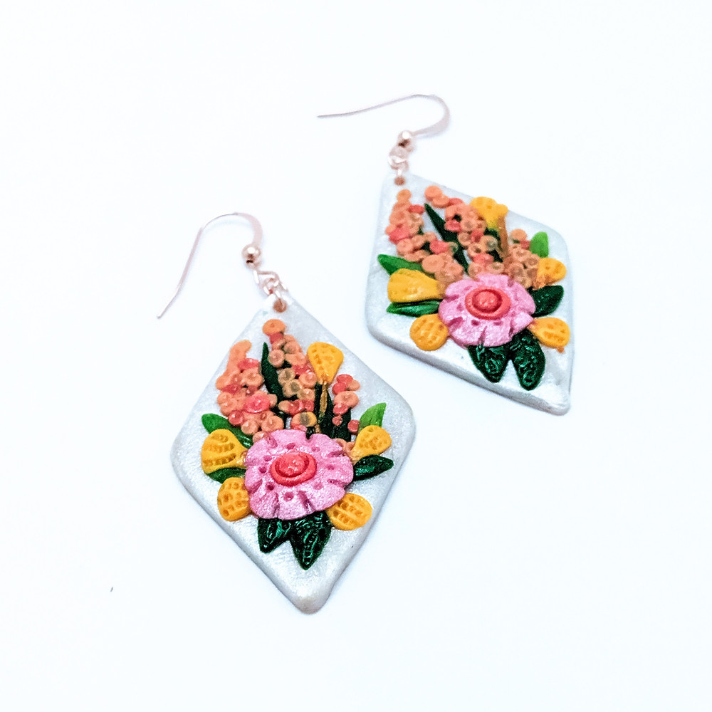 handmade earrings with white diamond background and pink and orange intricate floral details