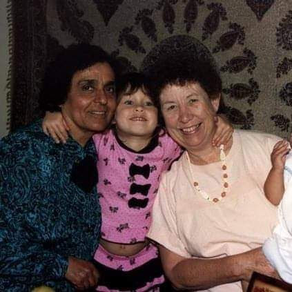 toddler Roya with her arms around both of her grandmothers