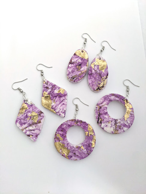 a trio of purple and gold leaf earrings