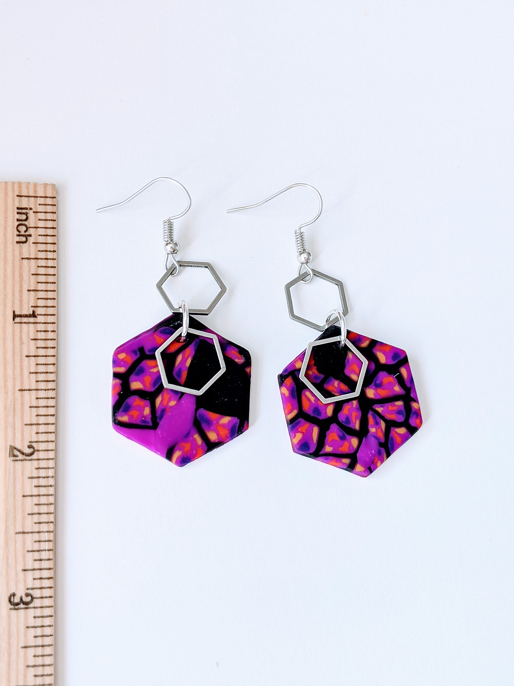 a pair of hexagon shaped earrings with purple and black design