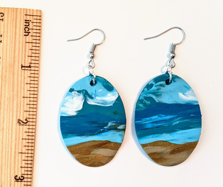 handmade clay earrings on white background. earrings are oval with abstract ocean.