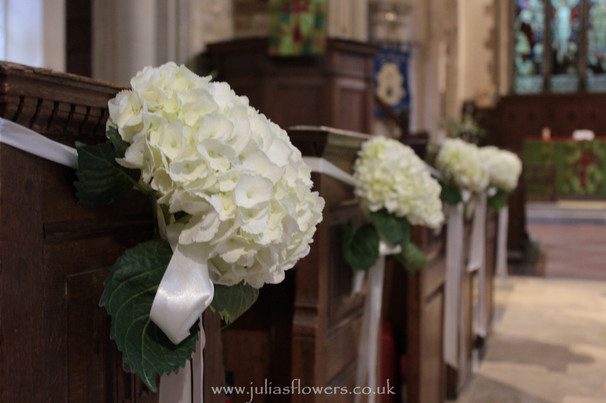 Hydrangeas tied to the Pew ends.JPG