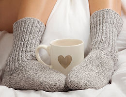 Two feet with socks and coffee cup