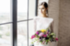 Bride at window in lace wedding gown