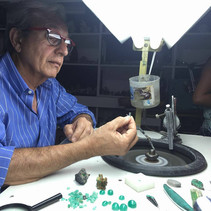 Mr. Hugo, un viajero italiano, examinando el proceso de pulido de esmeraldas.