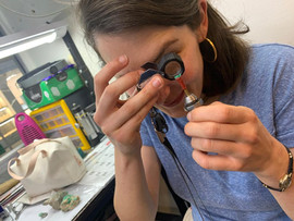 Miss. Burger examinando una esmeralda con una lupa 10x para joyeria