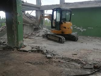 Гусеничный экскаватор разбирает здание. Аренда , Услуги экскаватора в Калининграде.