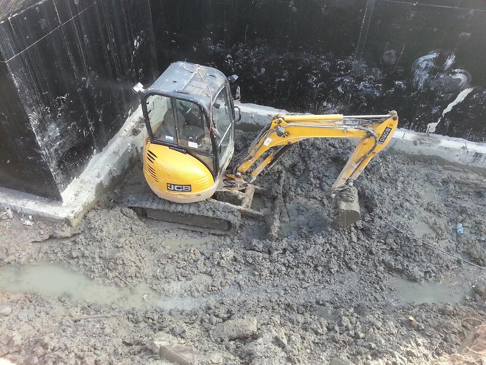 Мини экскаватор JCB8030 выполняет работу про рытью дренажной канавы в стесненных