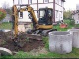 Мини экскаватор CAT 304 роет колодец глубиной 3м. и укладывает в него бетонные к
