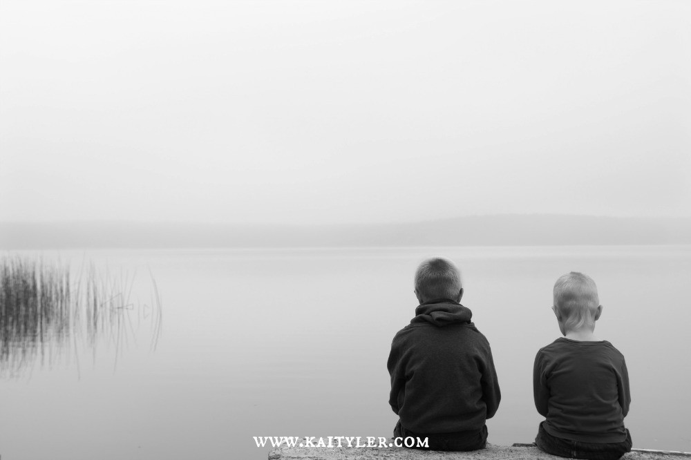 Two boys sitting by a lake