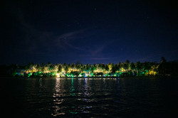 Perimeter lights illuminate the wedding for Abe and Megan's celebration as viewed from the sea