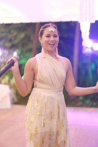 wedding host aziza with the party lights in the background.jpg