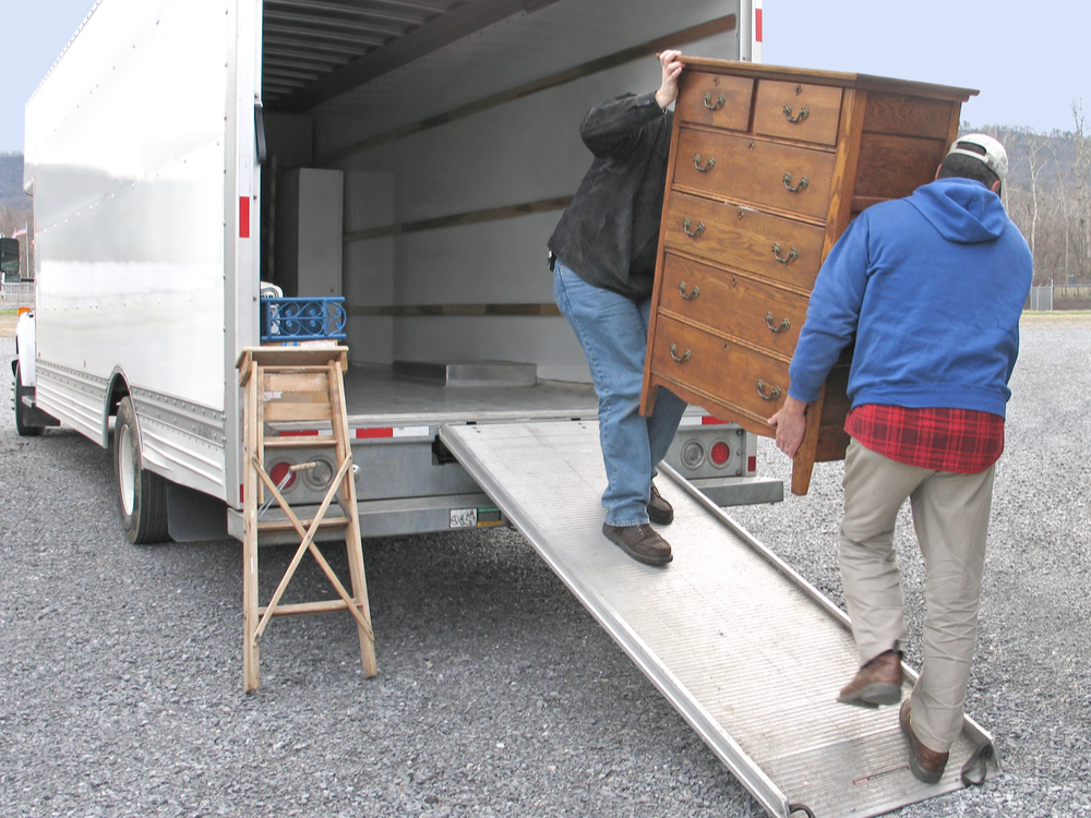 Two men carry chest of drawers easy onto a moving van