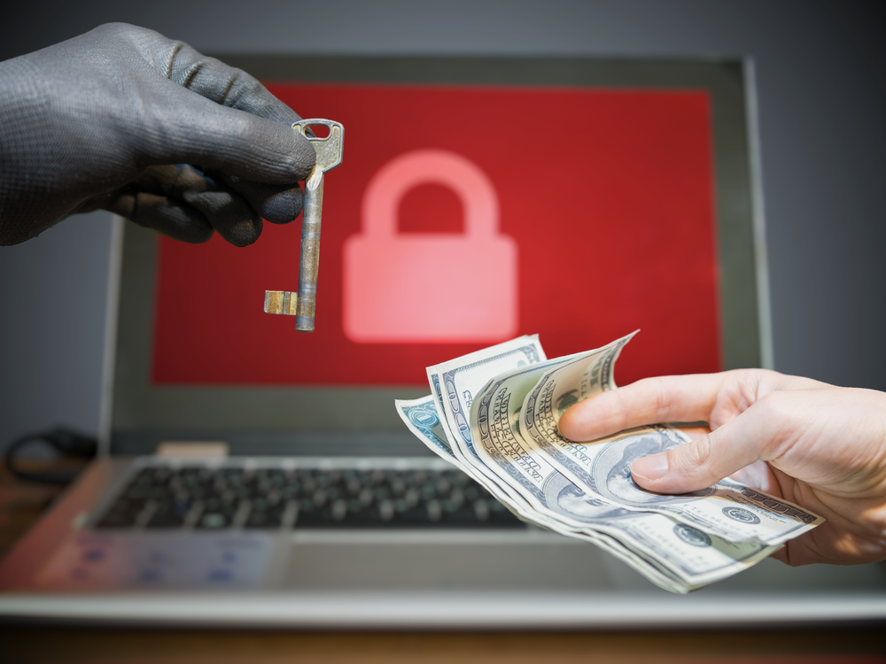 Computer security and extortion concept. Ransomware virus has encrypted data in laptop. Hacker is offering key to unlock encrypted data for money.
