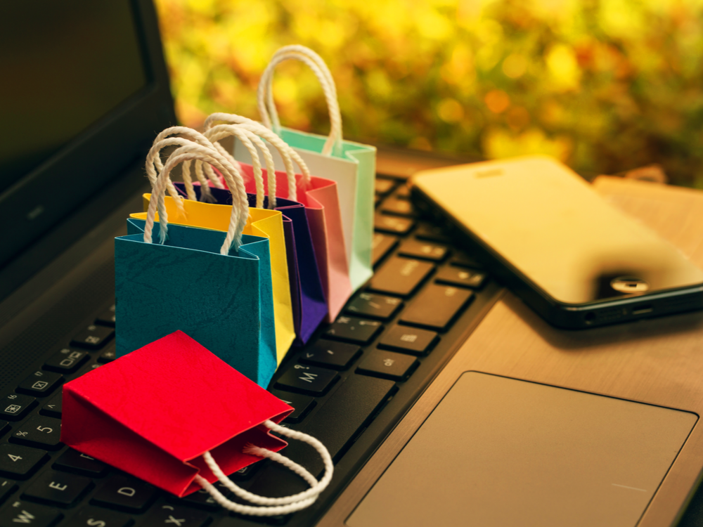 Six paper shopping bags and a smartphone on the notebook keyboard. Business concept about online shopping or order goods on the internet is more popular nowadays and can buy everything from home or office.