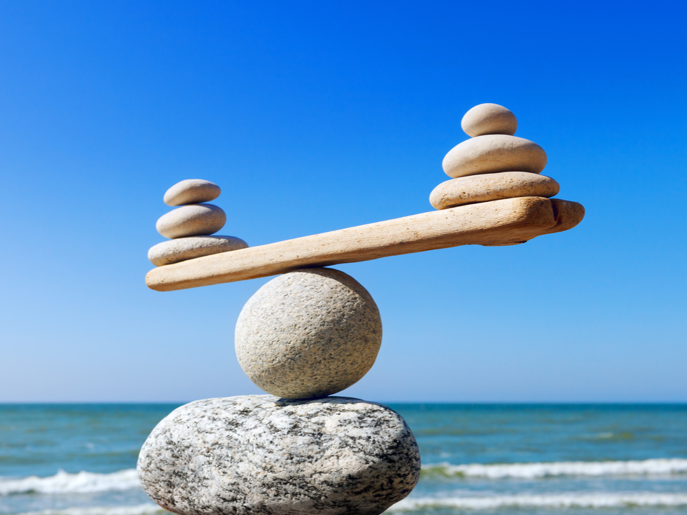 Symbolic scales of stones on the background of the sea and blue sky. Concept of harmony and balance. Pros and cons concept with Microsoft Dynamics