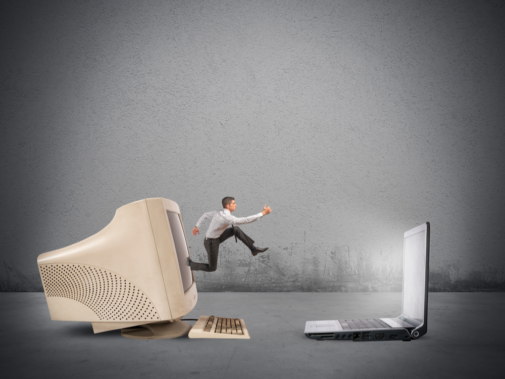 Businessman jumping from old computer to new laptop. Upgrade.