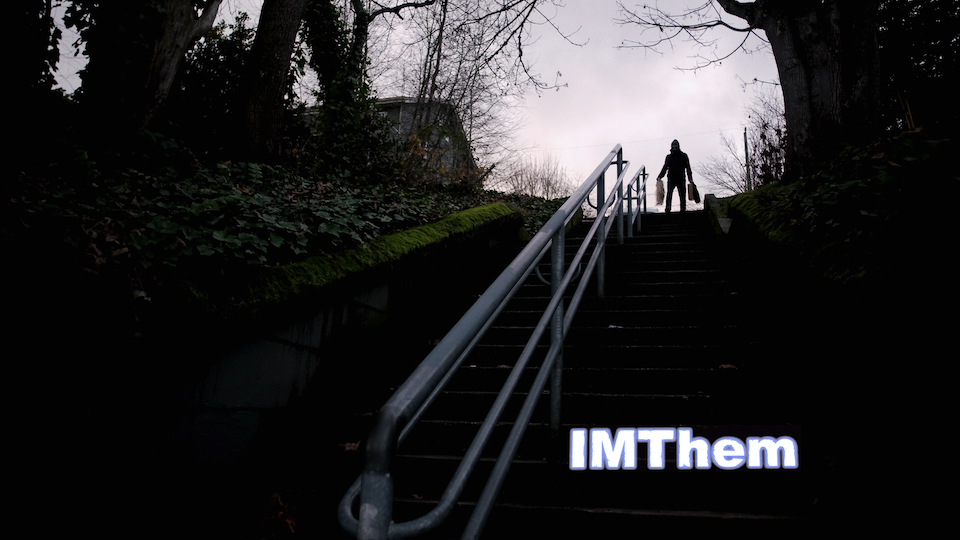 Low angle at the bottom of stairs outdoors with a silver railing and a male figure at the top wearing a black hoodie and carrying bags