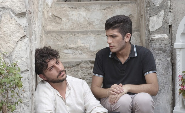 Two Italian men sit on steps; one looks off into distance and appears to have something on his mind and the other looks concerned about his companion