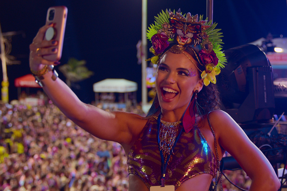 Social media influencer, Nina, poses for a selfie dressed in a vibrant carnival costume