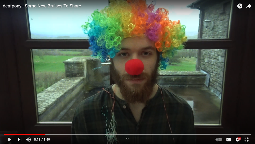 A young man looks directly into camera with straight expression, wearing red nose and colourful clown wig against a beautiful countryside backdrop