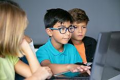 asian-boy-typing-laptop-keyboard-classmates-sitting-table-watching-him-doing-task-together