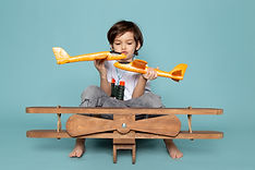 front-view-little-boy-playing-with-toy-planes-blue-floor.jpg