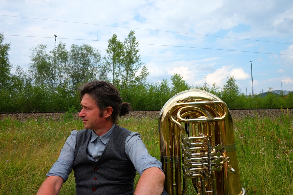 Ian sitting next to his Tuba in a field with a train line in the background