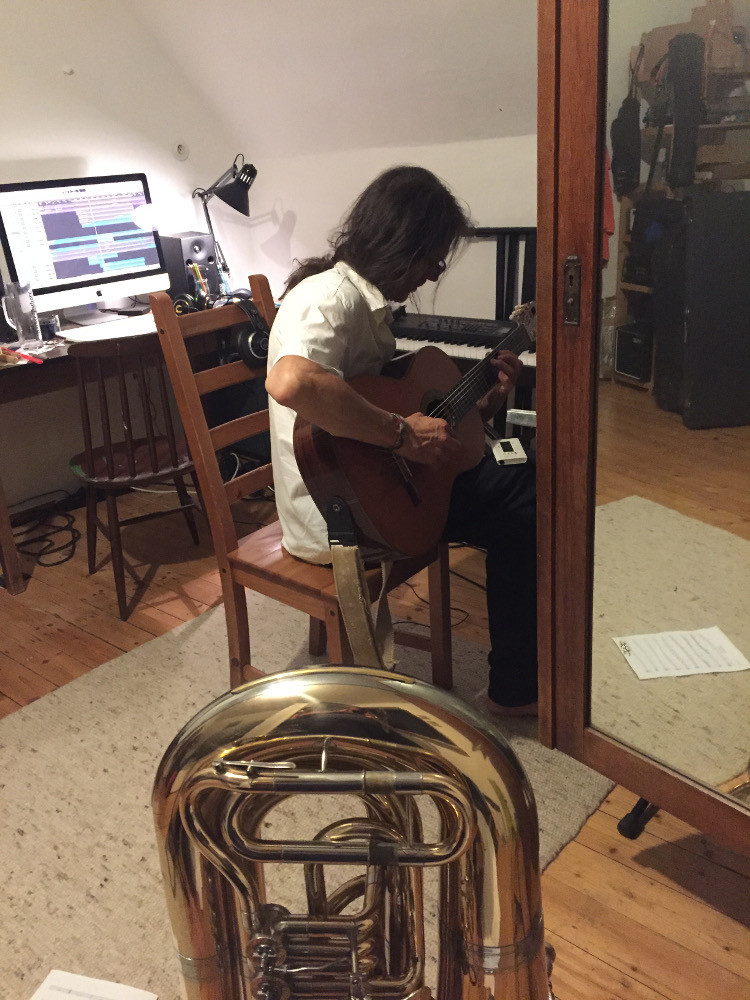 Dine Doneff (producer) sitting recording guitar in room with Tuba in front of a cupboard