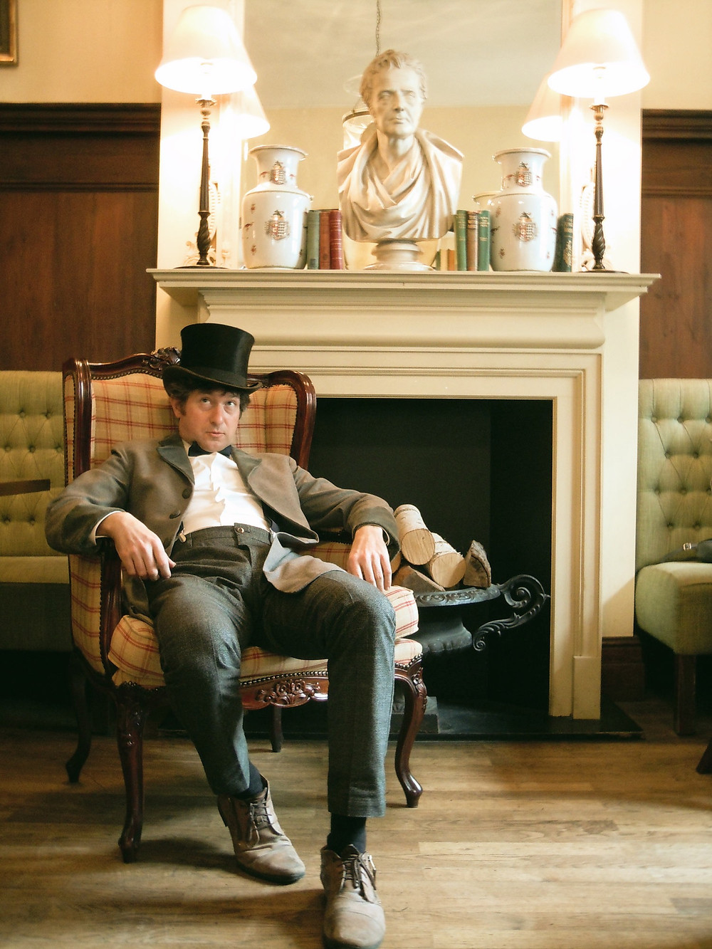 Ian Chapman in top hat and dinner attire slouching in chair deep in thought