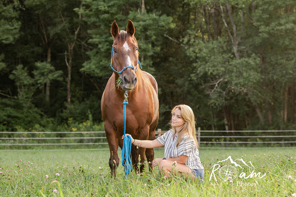 Girl sitting in the grass while her horse grazes.