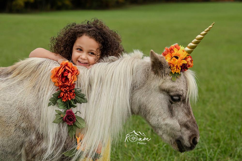 Little girl leaning on the pony unicorn