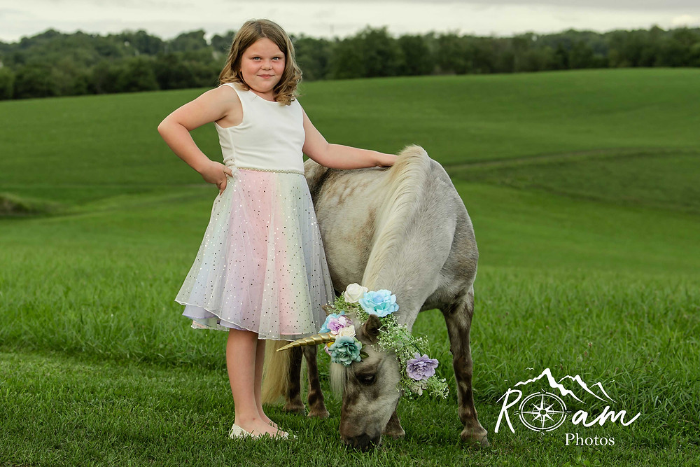 Little girl standing next to a pony/unicorn as it eats grass