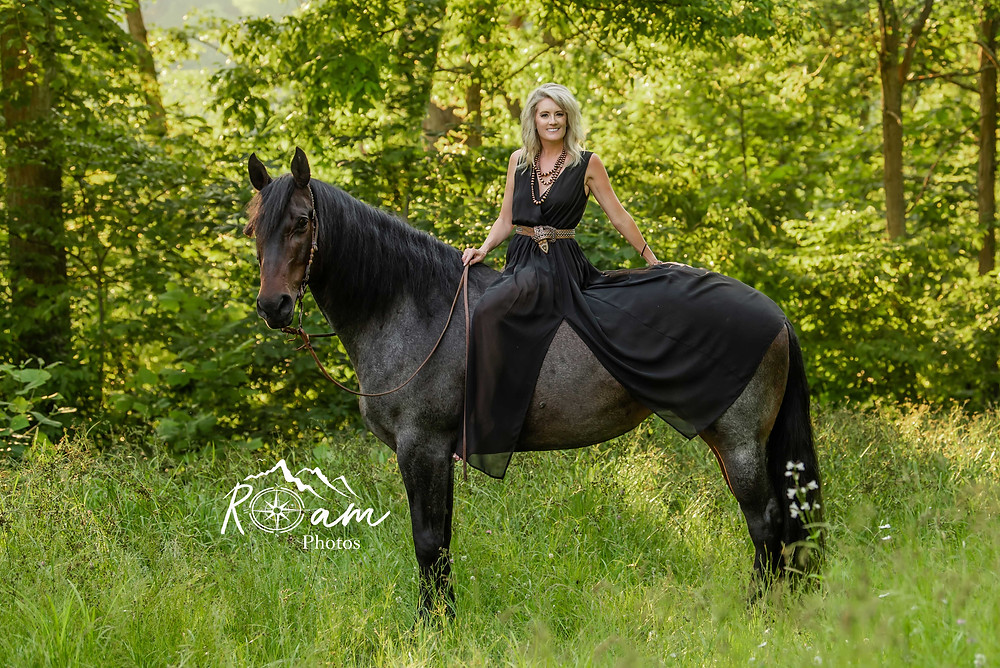 Woman in a black dress sitting on a beautiful horse