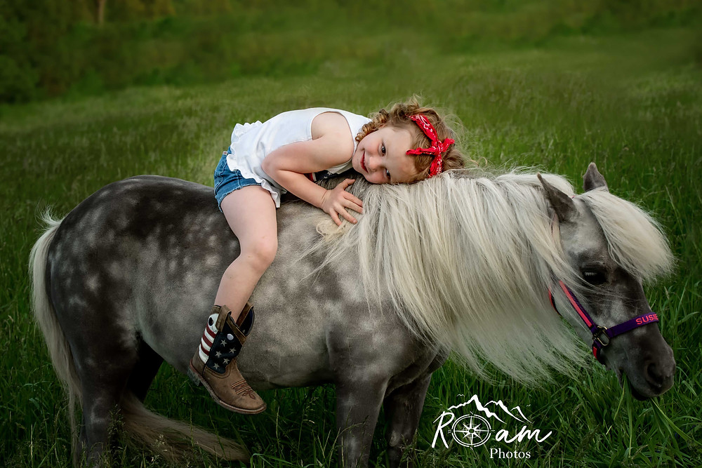 Little girl laying on her pony while giving her a hug