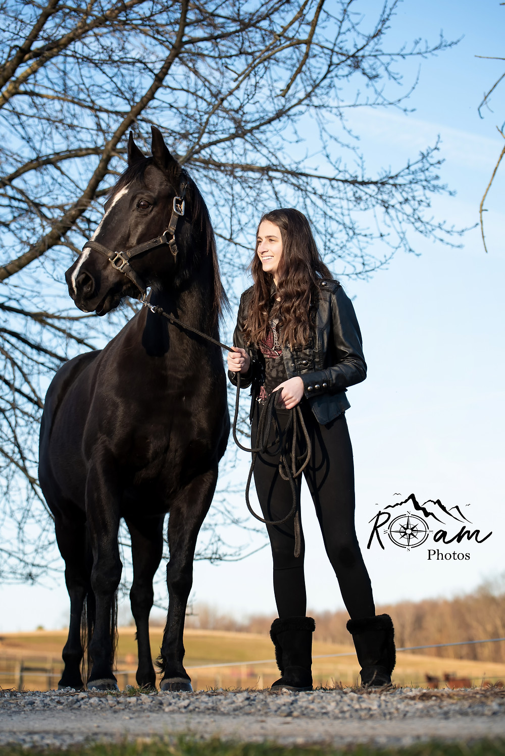 young girl holding black horse smiling