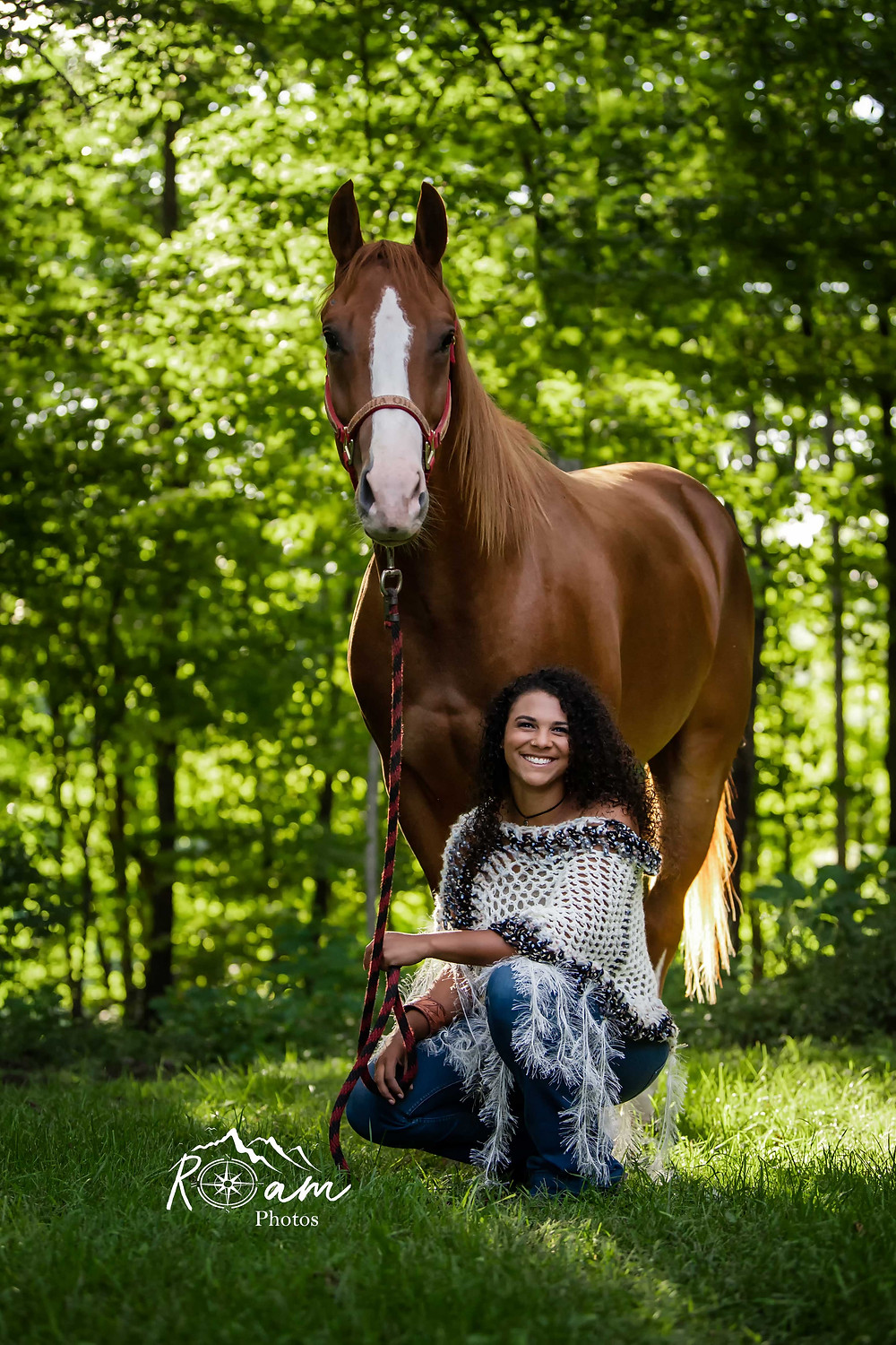 young woman squatting down in front of her horse