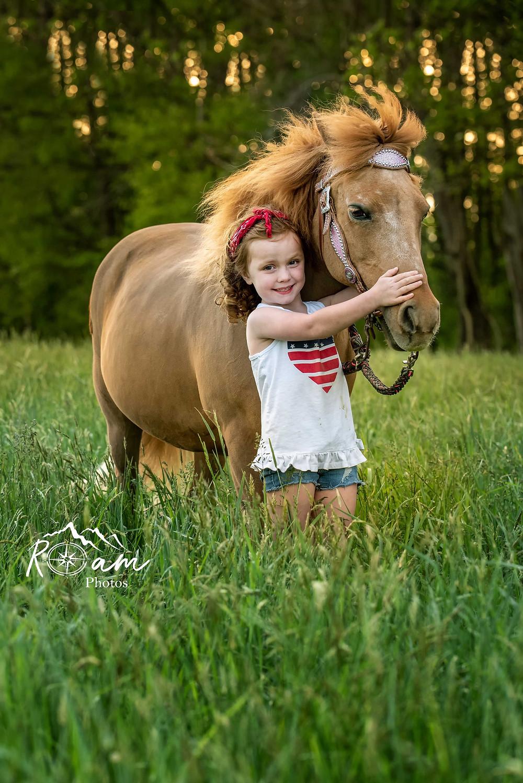 Little girl hugging her pony