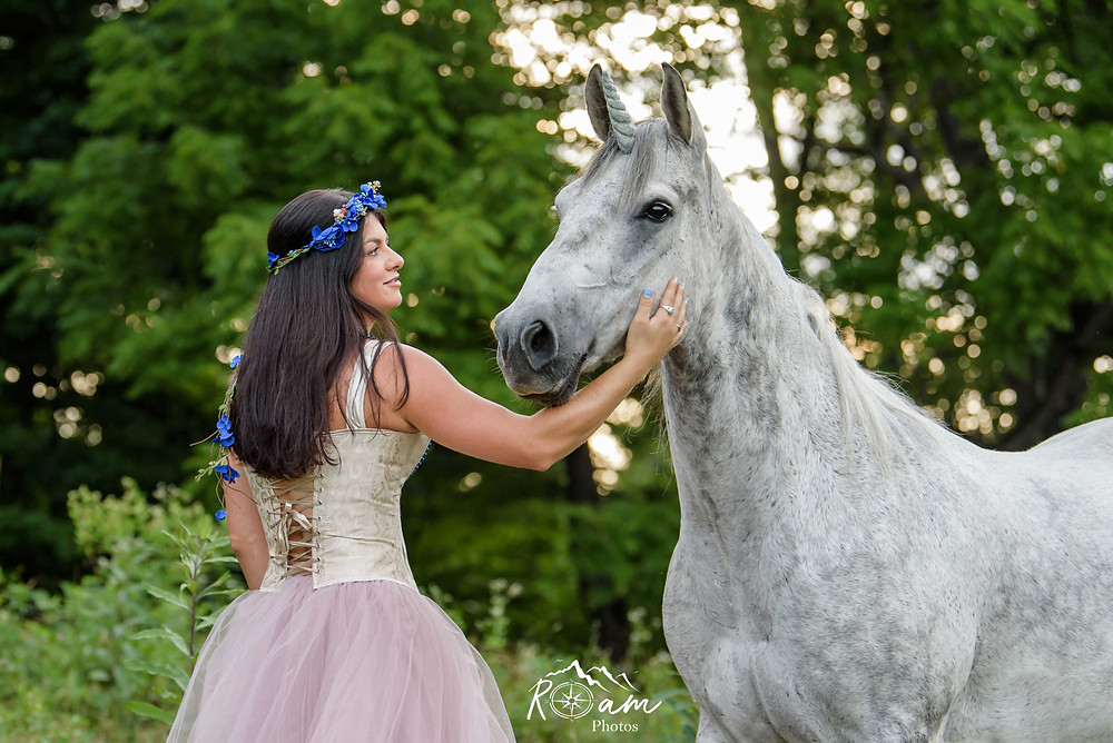 Woman in a princess dress with her horse as a unicorn