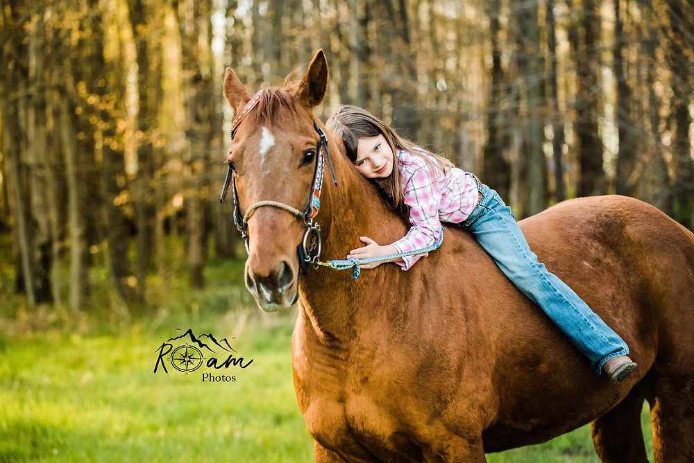 Young girl riding horse bareback while hugging her.