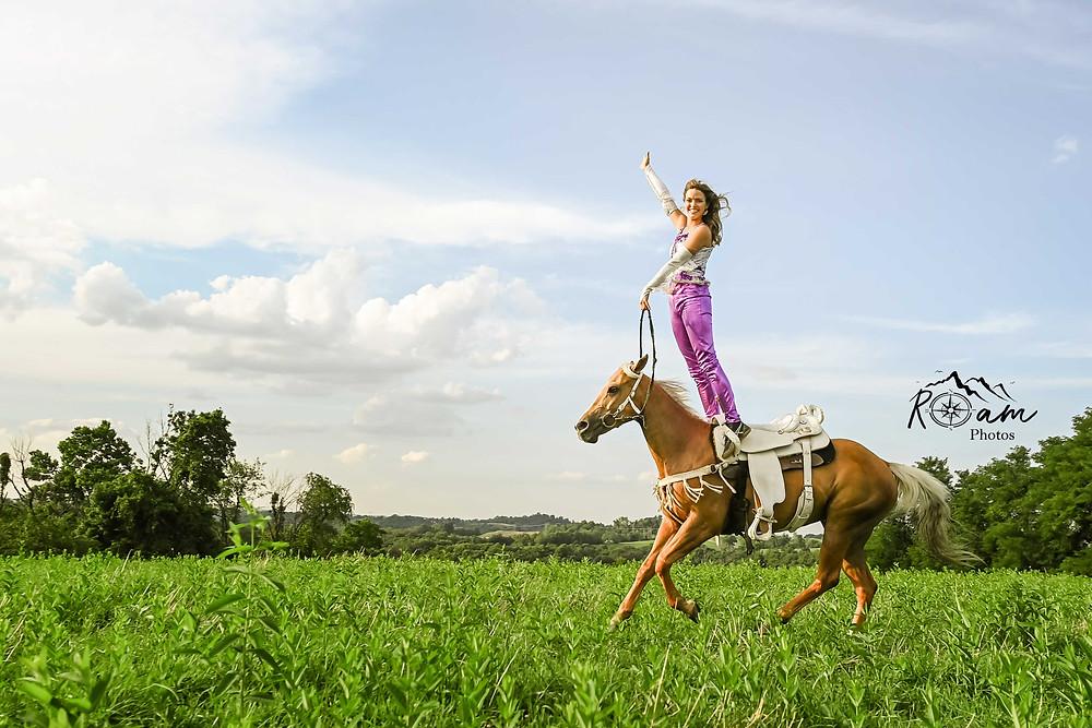 Beautiful girl standing on her running horse.
