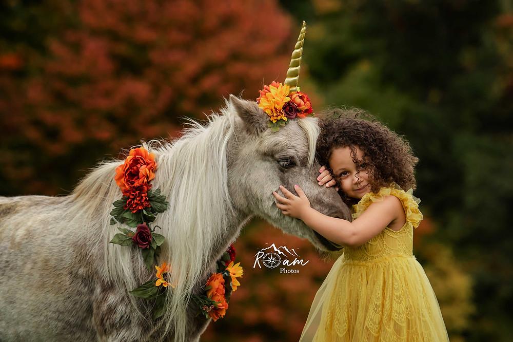 Little girl hugging a unicorn pony