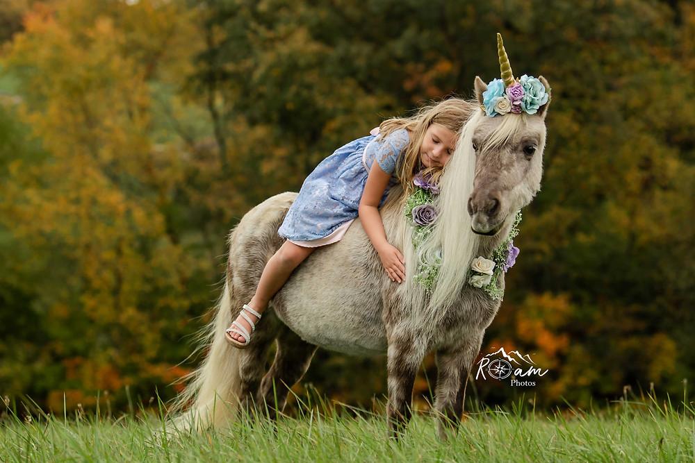 Little girl sleeping on a pony unicorn