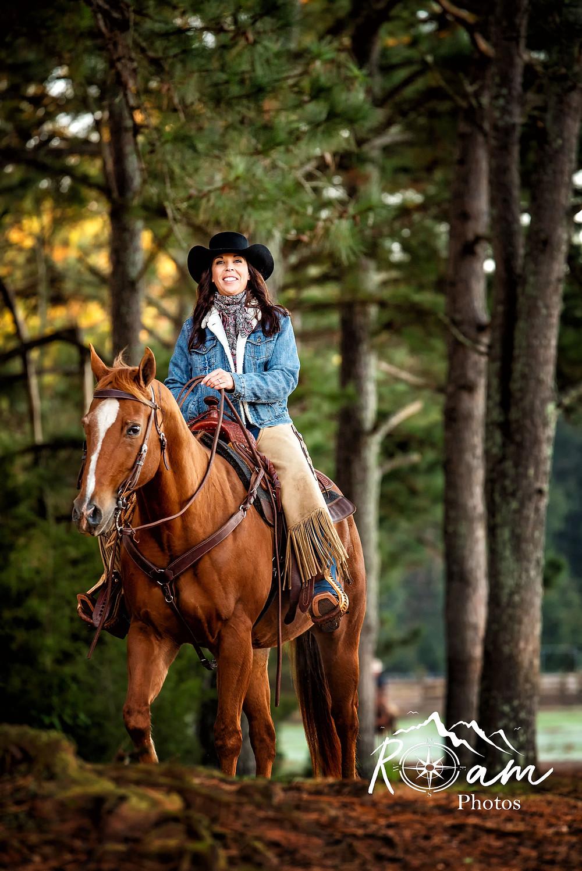 woman trail riding a sorrel horse