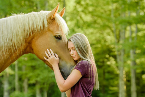 Young girl hugging her horse