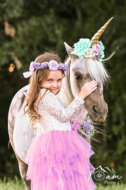 Little girl smiling petting a pony unicorn