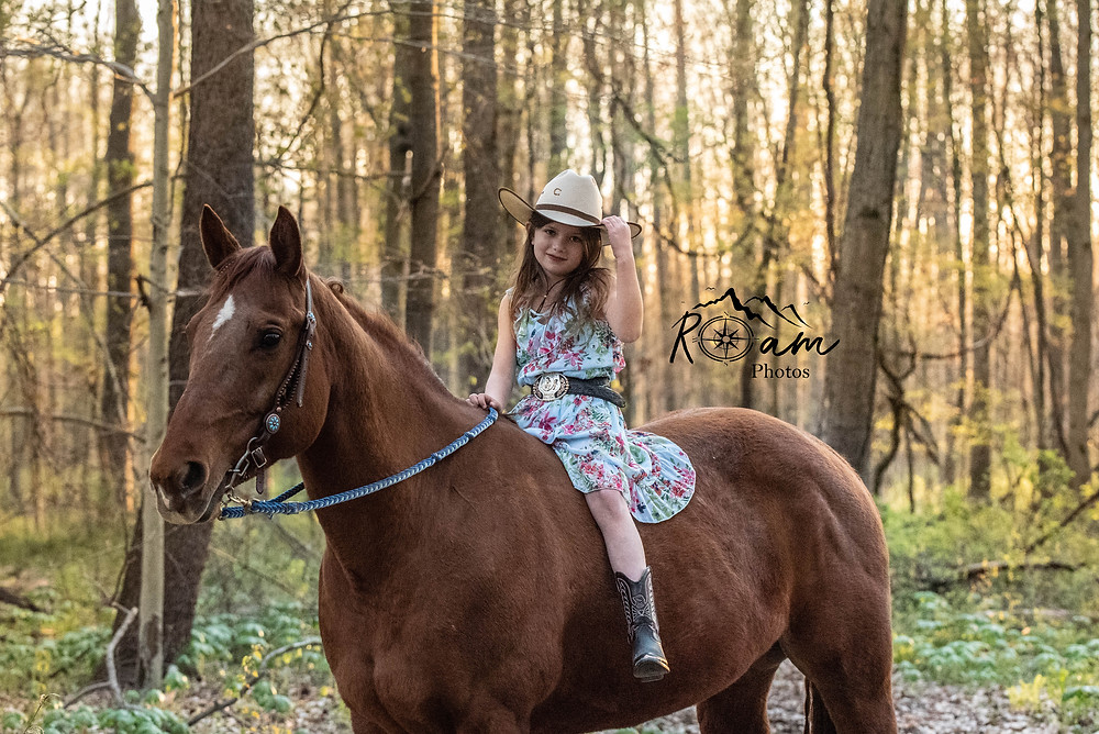Little cowgirl riding her horse tipping her cowgirl hat