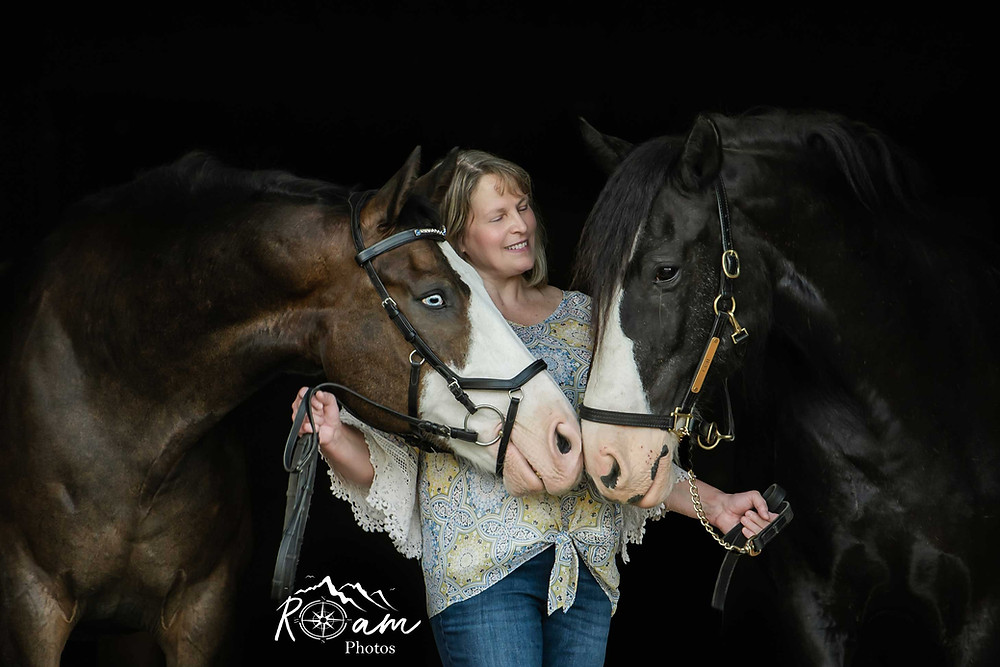 woman standing in the middle of two horses touching noses