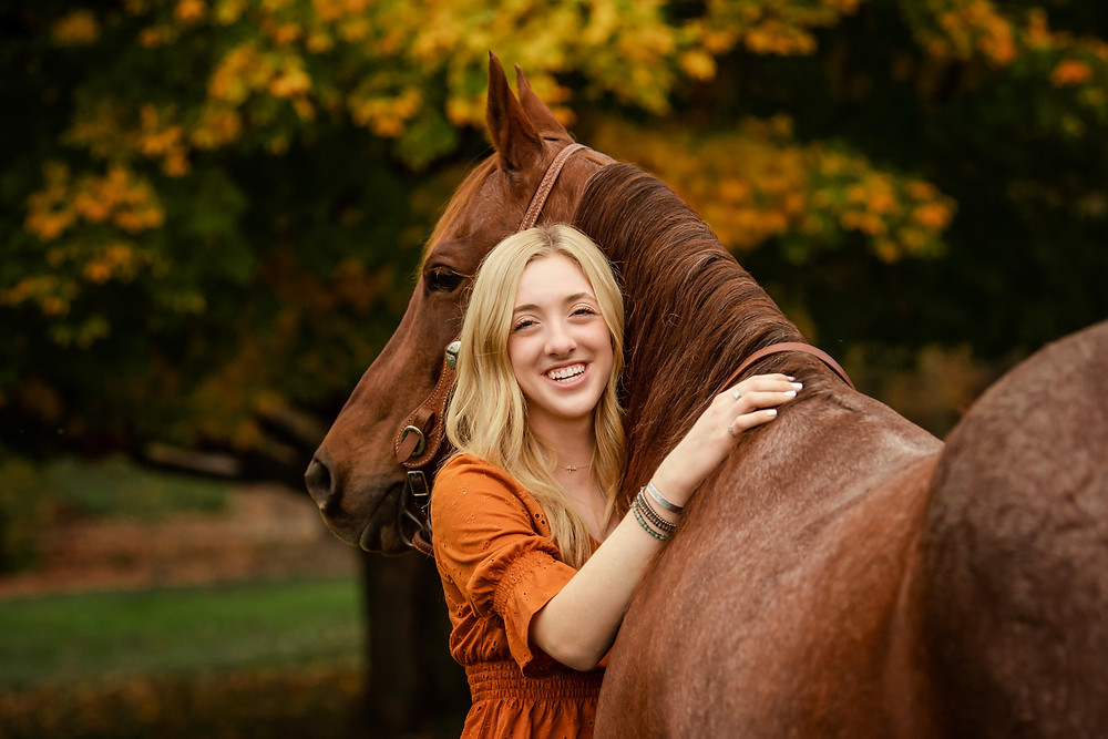 young girl hugging her horse.